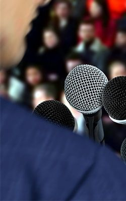 business man speaking into microphone to an audience
