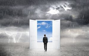 business man walking out of rain into sunny day by magical door