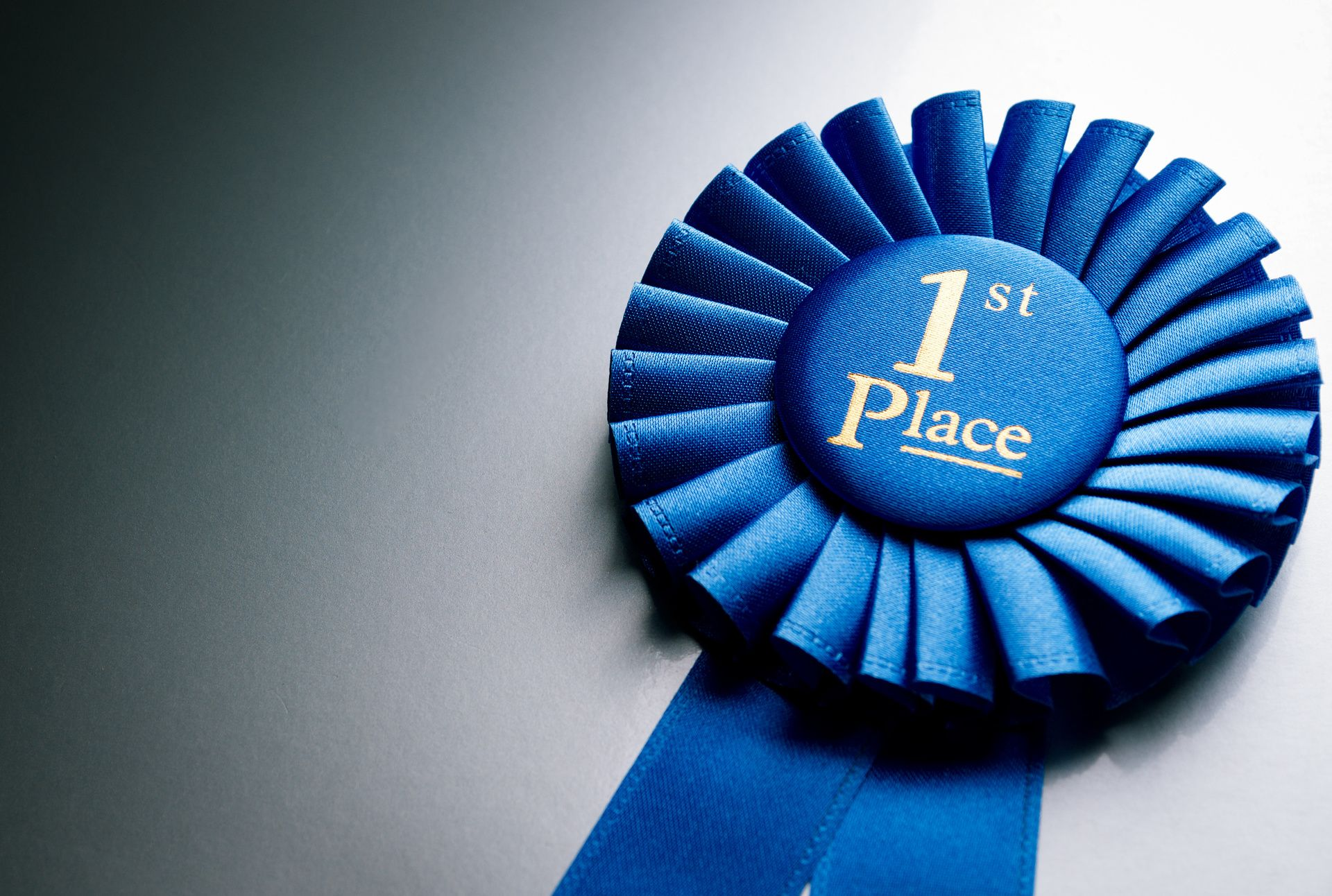 Blue first place winner rosette or badge from pleated ribbon with central text to be awarded to the winner of a competition on a graduated grey background